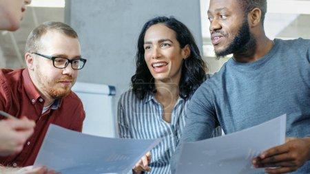 vielfältige Gruppe junger Fachleute umgibt Konferenztisch und gemeinsam versuchen, das Problem zu lösen.