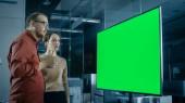"""Постер, картина, фотообои """"Мужские и женские бизнес Coworkers в зале имеют дискуссии о зеленый экран ключевые шаблон Chroma показаны на Tv презентации."""""""