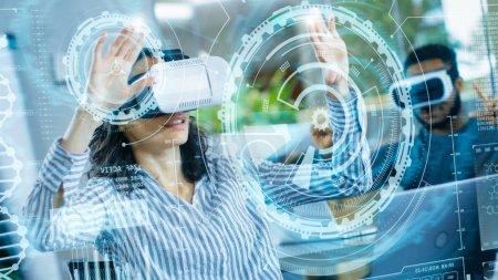 Photo pour Ingénieure en réalité virtuelle / Développeuse Porter un casque de réalité virtuelle crée du contenu avec ses collègues. Des jeunes brillants travaillent avec des hologrammes dans un projet de réalité augmentée et mixte . - image libre de droit