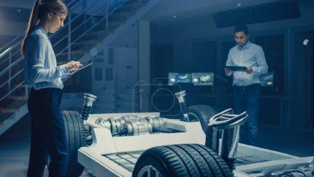 Photo pour Équipe d'ingénieurs automobiles travaillant sur la plate-forme de châssis de voiture électrique, prenant des mesures, travaillant avec le logiciel de CAO 3D, analysant l'efficacité. Cadre de véhicule avec roues, moteur et batterie - image libre de droit
