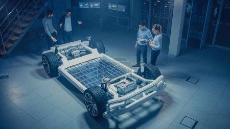Photo pour Équipe d'ingénieurs automobiles travaillant sur la plate-forme de châssis de voiture électrique, prenant des mesures, travaillant avec le logiciel de CAO 3D, analysant l'efficacité. Cadre de véhicule avec roues, moteur et batterie . - image libre de droit
