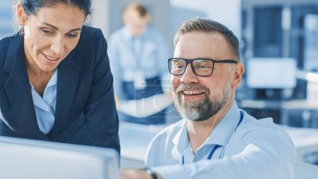 Photo for Female Chief Engineer Talks with Electronics Specialist, Explaining Things, He Works on Desktop Computer, they Smile. Modern and Bright Office with Stylish People - Royalty Free Image