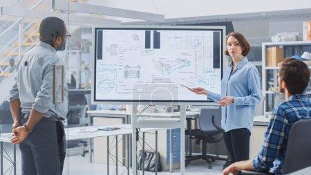 In Industrial Design Facility Team von Ingenieuren und Technikern haben ein Treffen, weibliche Spezialistin leitet Briefing, Gespräche und Zeichnungen auf digitalem interaktivem Whiteboard mit Auto-Prototypen-Konzepten