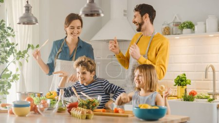 Photo for In Kitchen: Family of Four Cooking Together Healthy Dinner, Fool Around and Dance. Mother, Father, Little Boy and Girl, Preparing Salads, Cutting Vegetables. Cute Children Helping their Caring Parents - Royalty Free Image