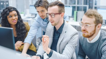 Im modernen Büro: Ein vielfältiges Team junger motivierter Geschäftsleute und Unternehmerinnen arbeitet am Computer, diskutiert, findet gemeinsam Problemlösungen. Ambitionierte Geschäftsleute