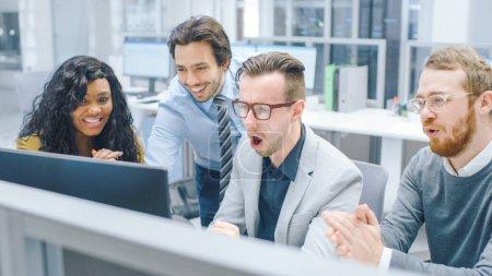 Im modernen Büro: Ein vielfältiges Team junger motivierter Geschäftsleute und Unternehmerinnen arbeitet am Computer, diskutiert, findet gemeinsam Problemlösungen und ist überrascht. Zusammenarbeit der Geschäftsleute