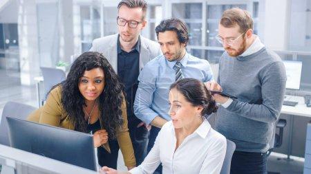 Im modernen Büro: Ein vielfältiges Team junger motivierter Geschäftsleute und Unternehmerinnen arbeitet am Computer, diskutiert, findet gemeinsam Problemlösungen. Ambitionierte Geschäftsleute und erfolgreiche Teamarbeit