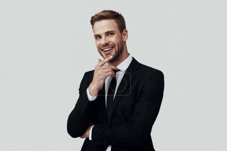 Photo pour Beau jeune homme en tenue de cérémonie regardant la caméra et gardant la main sur le menton tout en se tenant debout sur fond gris - image libre de droit