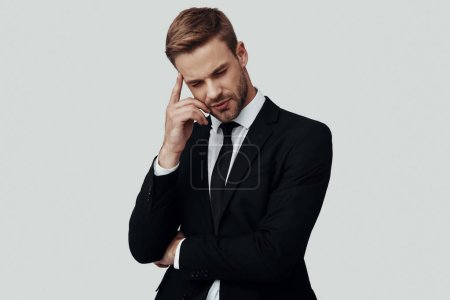Photo pour Beau jeune homme en tenue de cérémonie penser à quelque chose tout en se tenant debout sur fond gris - image libre de droit