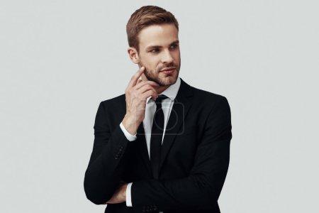 Photo pour Beau jeune homme en tenue de cérémonie regardant loin tout en se tenant debout sur fond gris - image libre de droit