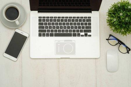 Foto de Mesa de trabajo de madera con ordenador portátil, teléfono inteligente y suministros.. - Imagen libre de derechos