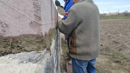 Photo pour Deux maîtres, constructeurs, mettre des pierres, construire une maison - image libre de droit