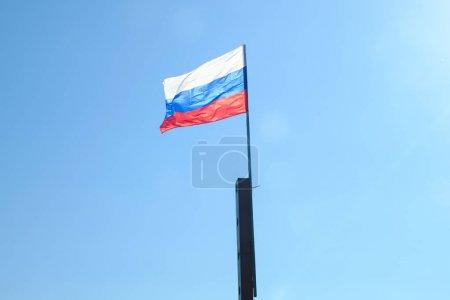 Photo pour Drapeau russe solitaire se développe dans le vent contre un ciel bleu - image libre de droit