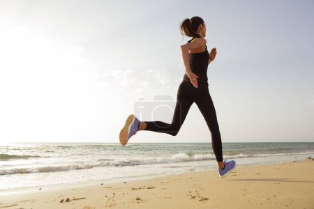 Photo for Young sport woman running in the morning on the beach. - Royalty Free Image