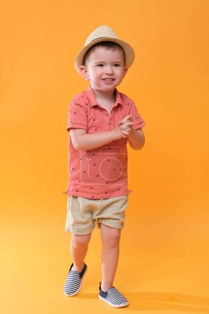 Photo for Very happy boy wearing summer outfit. Studio shoot on orange background. - Royalty Free Image