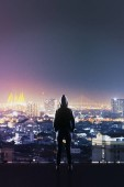 hacker's back silhouette standing on roof top and looking at night megapolis city