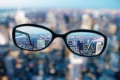 Close up of eyeglasses on blurry city background. Clean vision concept. 3D Rendering