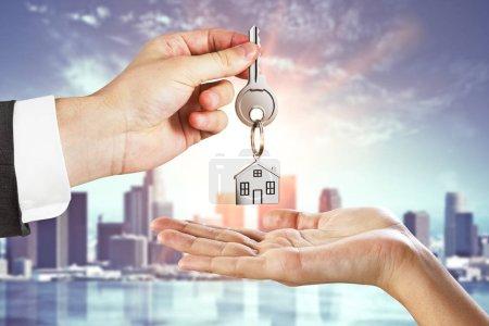 Photo pour Homme d'affaires, remise des clés sur fond de ville. L'immobilier et le concept de l'agent - image libre de droit