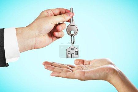 Photo pour Homme d'affaires, remise des clés sur fond bleu. Concept d'hypothèques et de la maison - image libre de droit