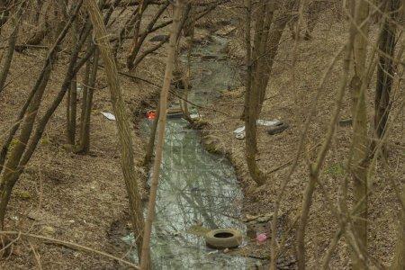 Photo pour Printemps forêt ruisseau rivière déchets plastiques pneus bouteilles en verre après la fonte de la neige. Enjeux environnementaux, pollution de la planète, collecte des déchets tri des déchets recyclage - image libre de droit