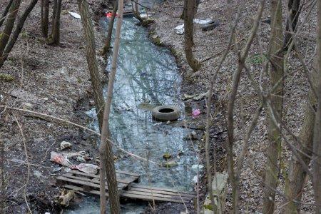 Photo pour Pollution des rivières et des réservoirs endommagés par les déchets, les problèmes environnementaux et la pollution de la planète. Rivière Dirty Creek au printemps après la fonte des neiges bouteilles de pneus plastique - image libre de droit