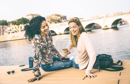Photo for Happy multiracial girlfriends having fun with mobile smart phone at park - Friendship concept with girls at wandering travel - Modern female lifestyle with women best friends - Vintage contrast filter - Royalty Free Image