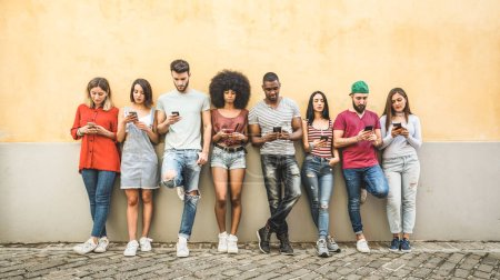 Photo for Multiracial friends using smartphone against wall at university college backyard - Young people addicted by mobile smart phone - Technology concept with always connected millennials - Filter image - Royalty Free Image