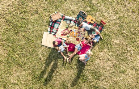 Photo for Aerial drone view of happy families having fun with kids at picnic barbecue party - Multiracial happiness and love concept with mixed race people playing with children at park - Warm bright filter - Royalty Free Image