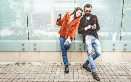 Photo for Happy hipster couple having fun with mobile smart phone at outdoors location - Friendship concept with best friends connecting and sharing content on social media - Millennial generation dating online - Royalty Free Image