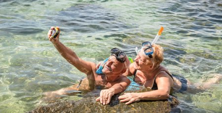 Photo for Happy retired couple taking selfie in tropical sea excursion with water camera and snorkel mask - Boat trip snorkeling in exotic scenarios - Elderly concept with active seniors traveling around world - Royalty Free Image