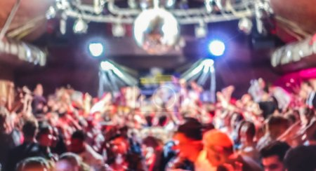 Photo for Blurred people dancing at music concert event - Abstract defocused background of disco club after party at live stage festival - Nightlife entertainment concept - Bright spotlight filter - Royalty Free Image