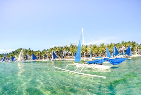 Photo for Small sailing boats for touristic excursions at sunset in Boracay island - Exclusive travel destination in Philippines - Vivid sunny filtered look - Royalty Free Image