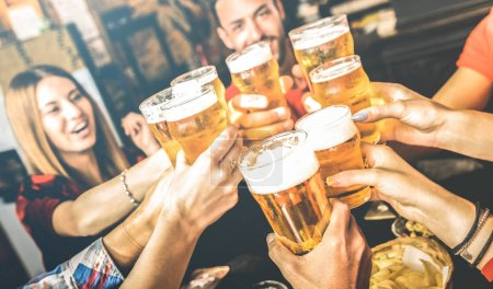 Photo for Friends drinking beer at brewery bar restaurant on weekend - Friendship concept with young people having fun together toasting brew pint on happy hour at pub - Focus on glass - Bright contrast filter - Royalty Free Image