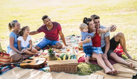 Photo pour Joyeuses familles multiraciales prenant selfie à pic nic garden party - concept de joie et d'amour multiculturels avec des gens métis s'amusant ensemble pique-nique barbecue avant le coucher du soleil - Filtre lumineux chaud - image libre de droit