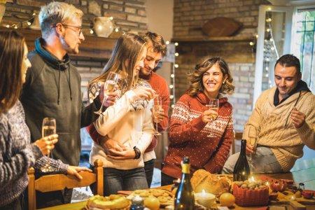 Photo pour Groupe d'amis heureux célébrant la fête de Noël avec du vin blanc et de la nourriture sucrée au souper - concept de vacances d'hiver avec des jeunes profitant du temps et s'amusant à manger ensemble - Filtre chaud - image libre de droit