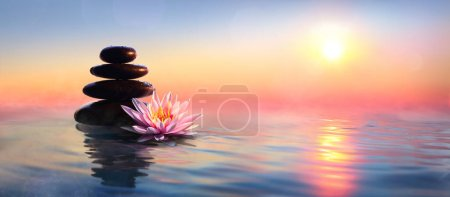 Photo pour Concept zen - pierres de spa et nénuphars dans le lac au coucher du soleil - image libre de droit