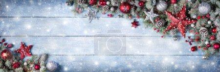 Photo pour Ornement de Noël avec branches de sapin sur planche en bois enneigée - image libre de droit
