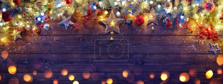Photo for Christmas Ornament With Fir Branches And Lights On Dark Wooden Plank - Royalty Free Image