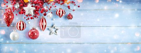Photo for Christmas Ornaments And Berries Hanging On Snowy Wooden Plank - Royalty Free Image