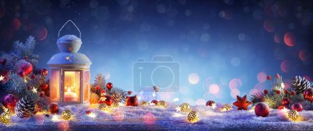 Photo for Christmas Lantern On Snowy Table With Fir Branches And Ornaments - Royalty Free Image