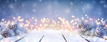 Photo pour Fir Branches And Pinecones On Snowy Table And Christmas Lights - image libre de droit