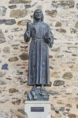 Guadalupe, Spain - September 3th, 2017: Francis of Assisi bronze statue at Guadalupe Monastery entry. Caceres, Extremadura, Spain