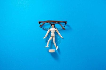 Photo pour Mannequin en bois humain avec lunettes de vue sur fond bleu. Photographie conceptuelle d'un problème de mauvaise vision. Idée minimale et créative . - image libre de droit