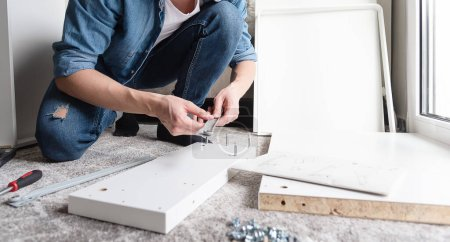 Photo for Concentrated young man choosing tools for assembling new furniture for home - Royalty Free Image