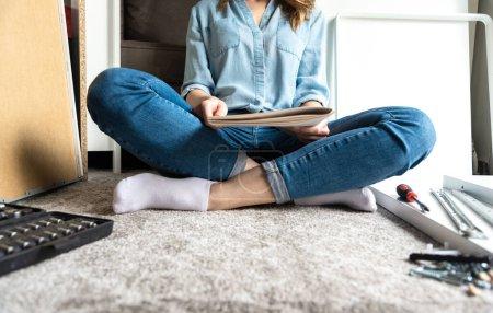 Photo pour Instructions de lecture femme pour assembler des meubles à la maison - image libre de droit