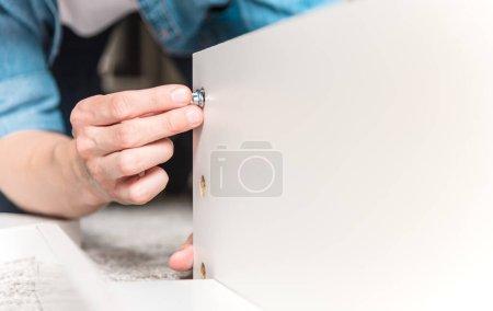 Photo pour Vue rapprochée du jeune homme assemblant de nouveaux meubles à la maison - image libre de droit