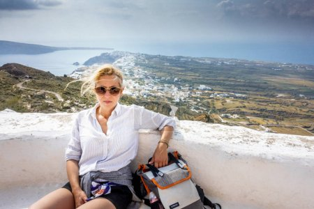 Relaxed female hiker overlooking Oia town