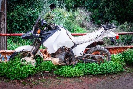 Photo pour Moto de style rétro stationné près de la clôture sur rue - image libre de droit