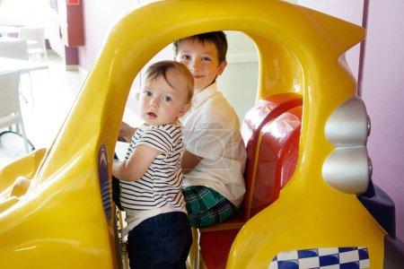 Photo for Two little boys sitting in amusement park ride - Royalty Free Image