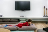 Boy watching on mobile while lying down on sofa at Crete, Greece, Europe